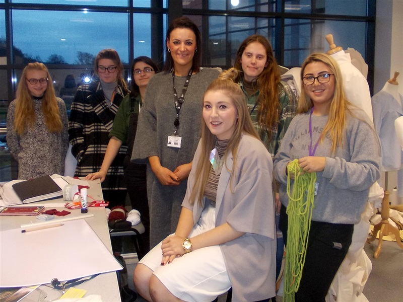 Lottie Coleman (seated) with some of the fashion students and course leader Angela Devoti (centre).