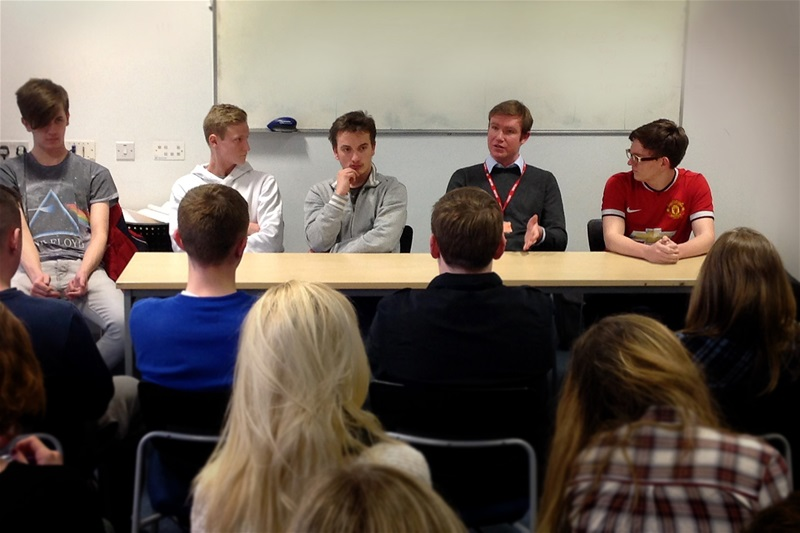Tim Roca (sat at table, third from left) debates with the students